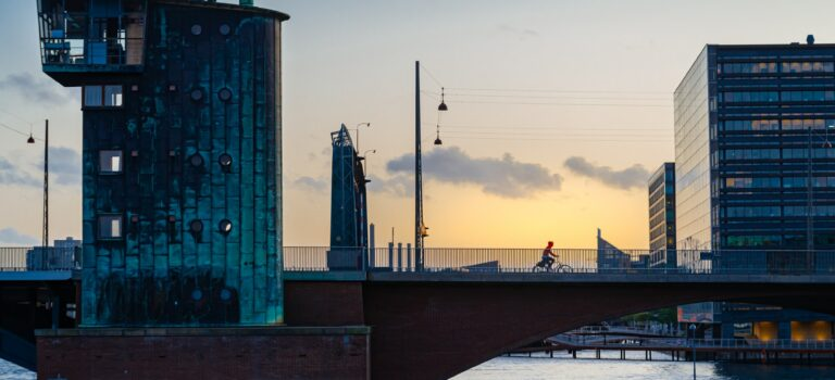 Silhouette of a Person Riding a Bicycle Over the Bridge in Sunset