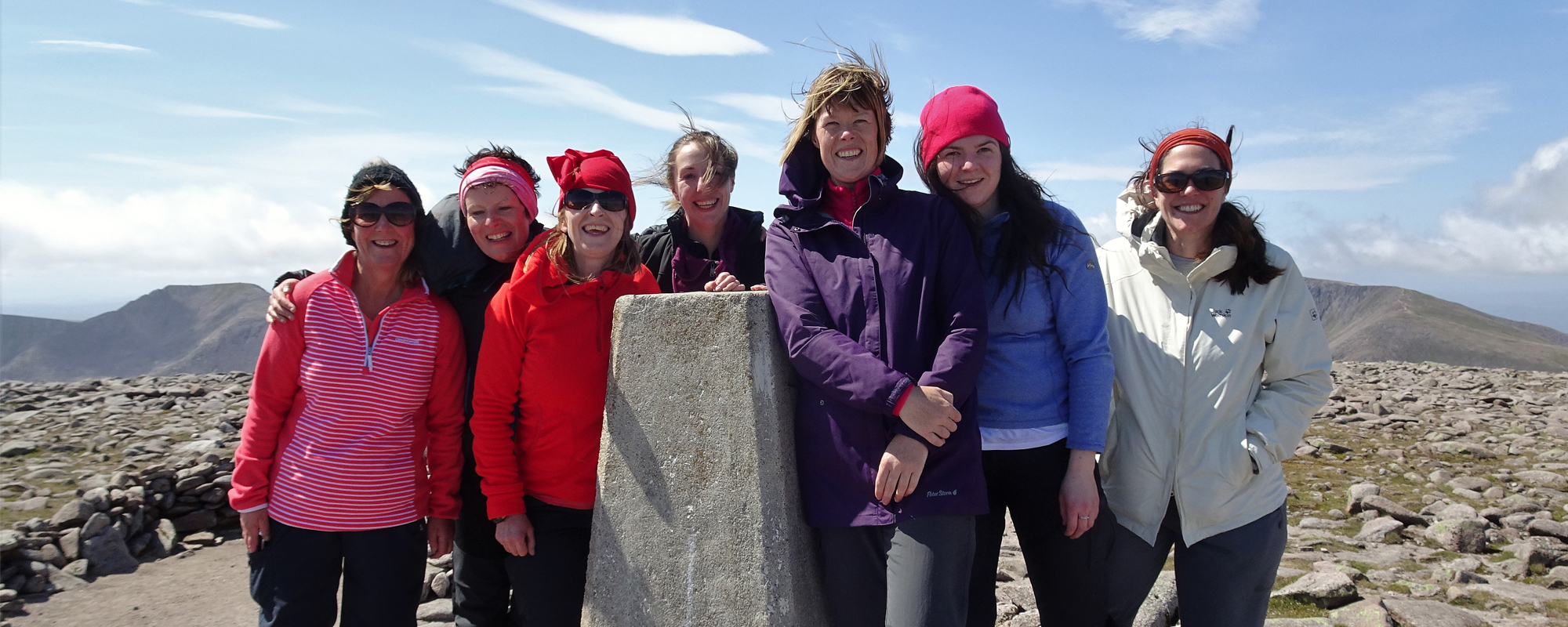 A group of women smile on a mountain summit in the Cairngorms