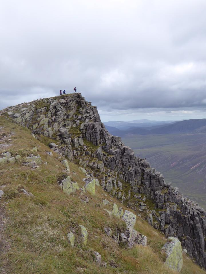 Trekkers stand at the summit of Sgor Goaith in the Cairngorms