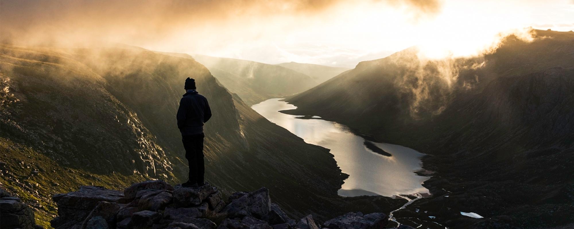 A trekker gazes over Loch Avon in the Cairngorms at sunset