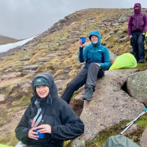 Female trekkers enjoy a hot drink in the rain in the Cairngorms
