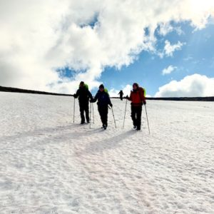 Female trekkers walk over remaining snow in the high Cairngorms