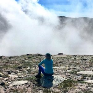 Woman sits on the Cairngorm plateau in deep thought