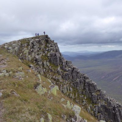 Female trekkers look over Loch Eanaich from Sgor Gaoith in the Cairngorms