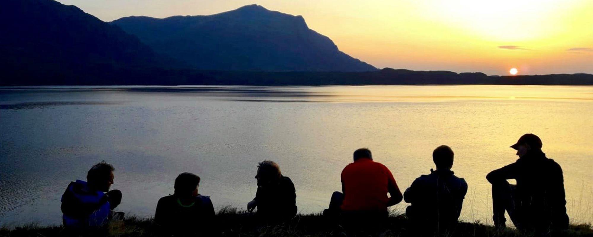 A group of men watch the sunset over a loch in Scotland