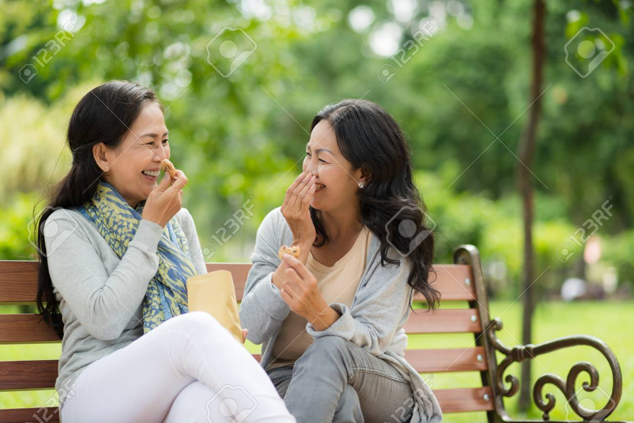 77258595-mature-asian-female-friends-chatting-and-eating-cookies-outdoors.jpg