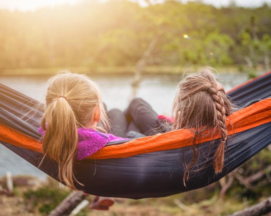 2 børn i en hængekøje kikker ud på en sø.