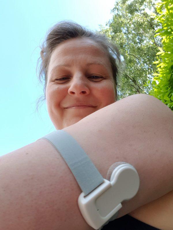 Foto af Thea Drachen smilende og kikker ned på sin arm, hvor der sidder en Miaomiao 2.