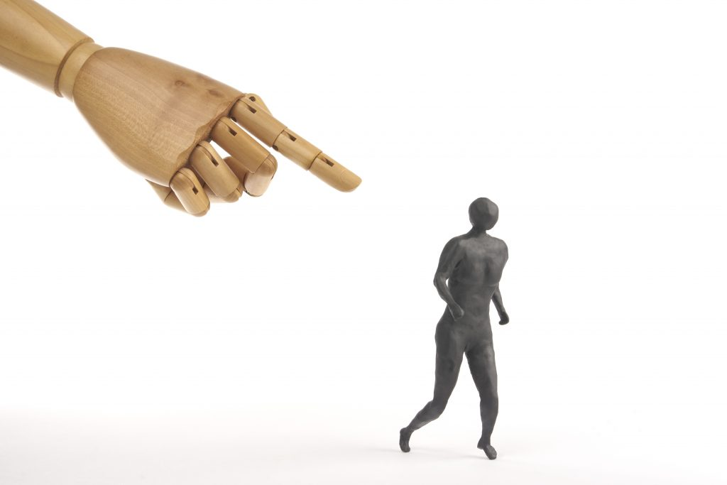 A white mannequin hand pointing at a black figure