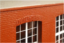 Fasaden är tillverkad av 12mm tjocka plywoodskivor med sand och spackel utanpå. Tegelstenarna är ingraverade för hand, en och en. Varje sten är mindre än en kvadratcentimeter.