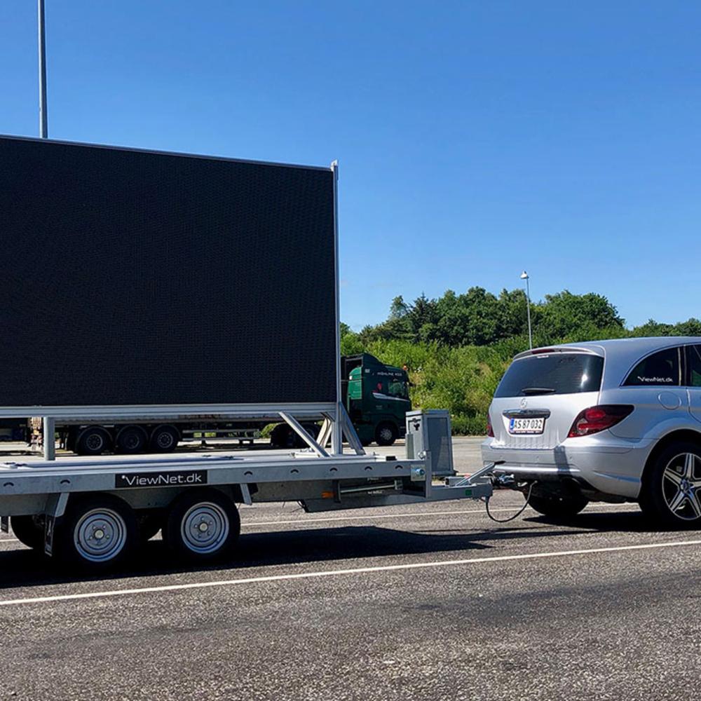 Mobil storskærm spændt på en trailer bag en bil på vej ud til arrangement