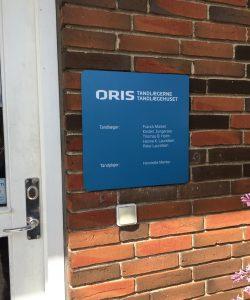 Metalskilt monteret ved dør. Kunde: Oris Tandlægehus.