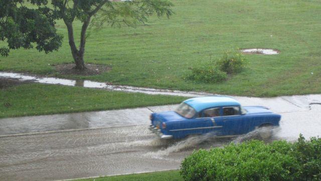 Blauer Oldtimer in Kuba ist trotz starkem Regen unterwegs.