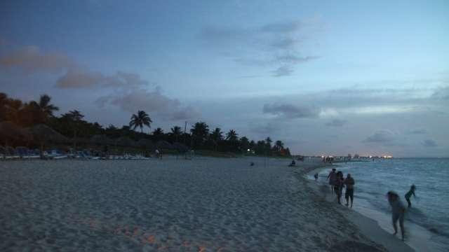 Ein breiter Sandstrand mit Palmen. Junge und alte Menschen genießen die letzten Sonnenstrahlen am Meer in Varadero.