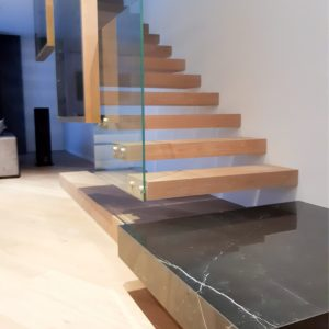 Trætrappe i børstet eg, svævetrappe med stålvange indbygget i væg, gelænder i glas og marmor