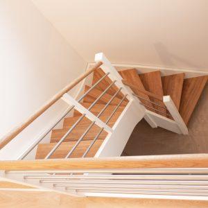 Trætrappe i eg, kvartsvingstrappe set oppefra, medløbergelænder og trappeværn i rustfri stål med håndliste af eg