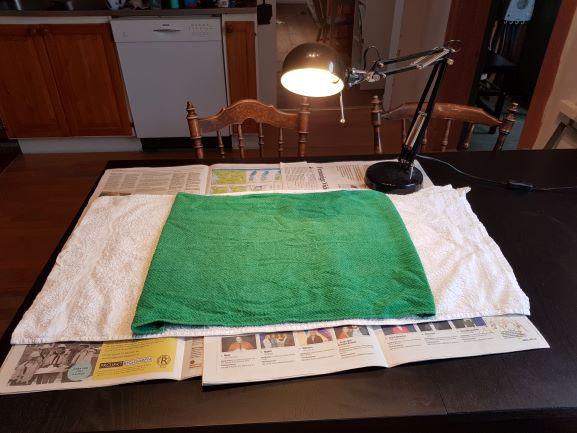 Tidningar på ett bord med en grön handduk ovanpå. En svart lampa till höger som ger ett bra ljus. Bra undersökningsplats och operationsplats för kastration av katt.