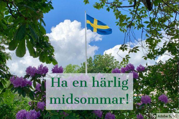 """En svenska flagga på flaggstång mot en blå himmel med lite vita moln. Trädgrenar från ett kastanjeträd och blommande lila rododendron syns i förgrunden. Texten """"Ha en härlig midsommar!"""""""