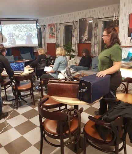 Miljö från Café Linnea där förberedelser för filmvisning från youtube pågår. Agneta Andersson står till höger i bild och har haft sin presentation på tisdagscafé redan.