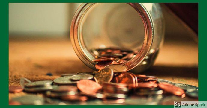 En liggande glasburk med mynt som har fallit ut ur den. Bilden ska symbolisera priser.