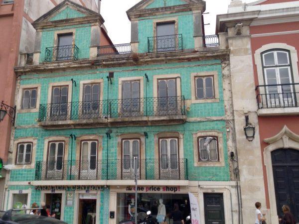 Fachada revestida en azulejo vidriado turquesa con flores estilizadas. Plaza República, 14