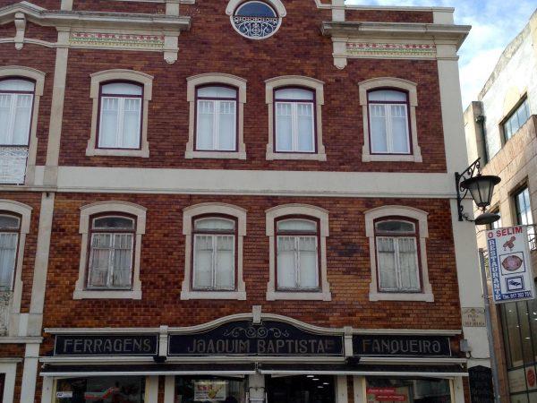Edificio con revestimiento de azulejo rojo oscuro vidriado. Plaza República, 95