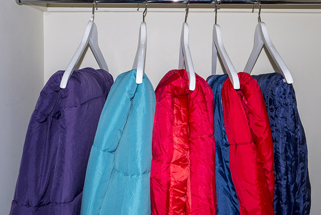 How to Choose a Sleeping Bag - 5 sleeping bags hung in a wadrobe on white wooden hangers