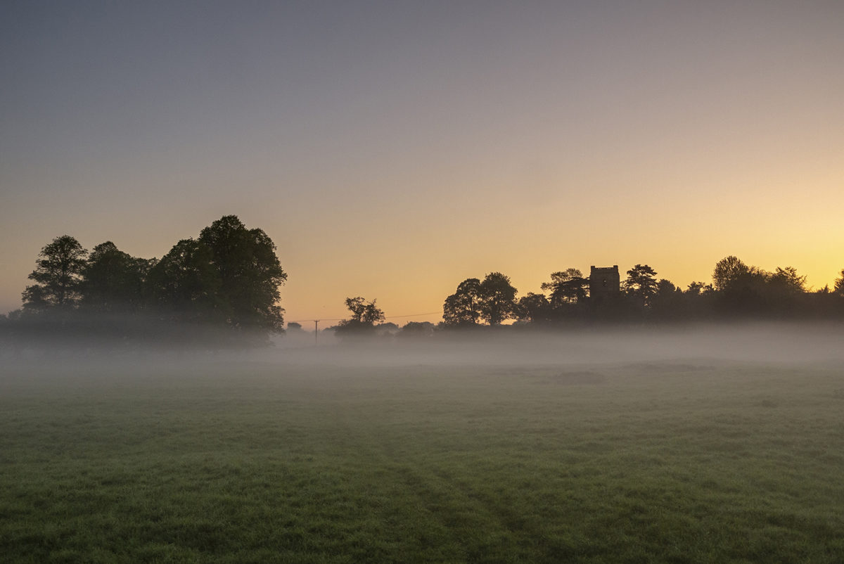Holy Trinity Church in Old Wolverton, across misty fields.