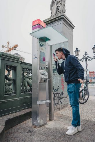 man wearing blue jeans and jacket shouting at a telephone booth