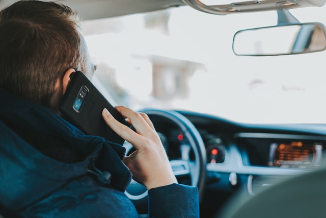 man answering a call in his car