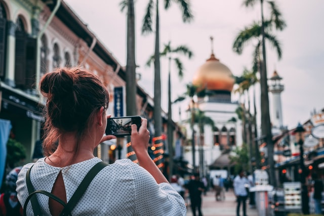 woman taking a photo of a beautiful scenery using her phone