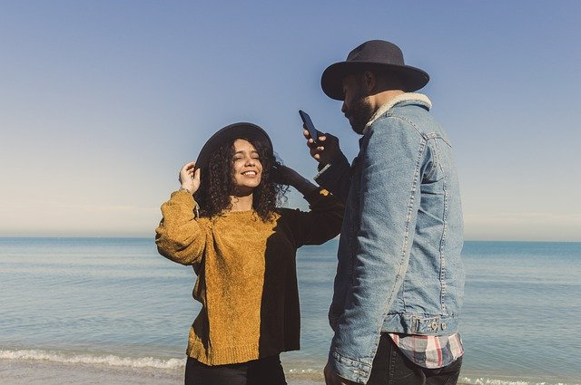 man taking photo of a woman using a phone
