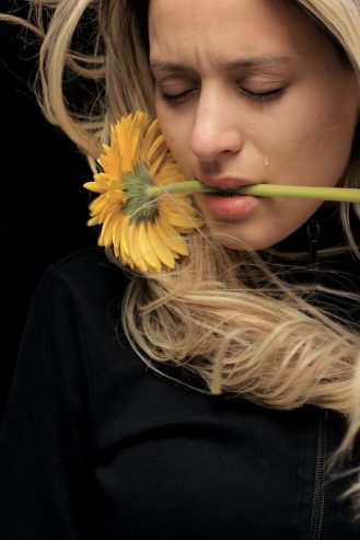 woman with sunflower in her mouth crying