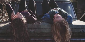 girls lying on a car