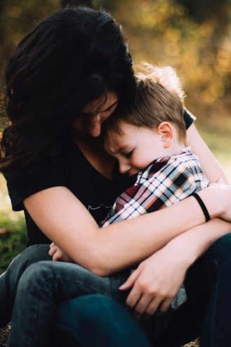 mom with her son on her lap crying