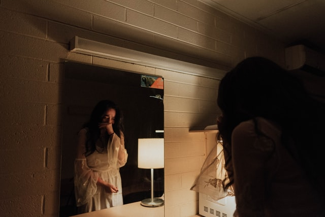 woman crying facing the mirror