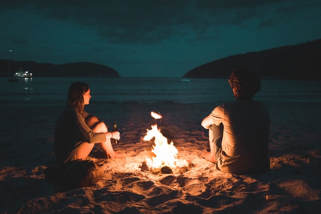 man and woman having bonfire in the beach