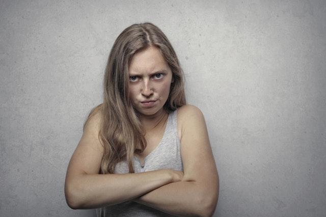 woman in gray tank top looking furious