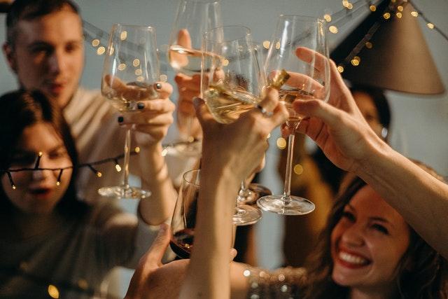 people cheering wine glasses