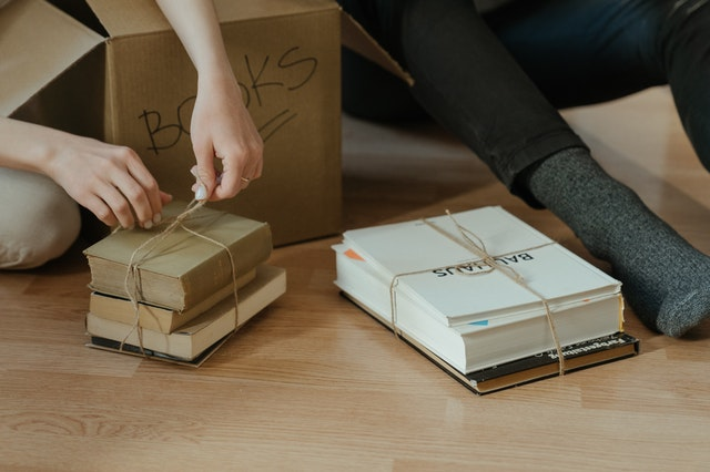 person holding brown cardboard box