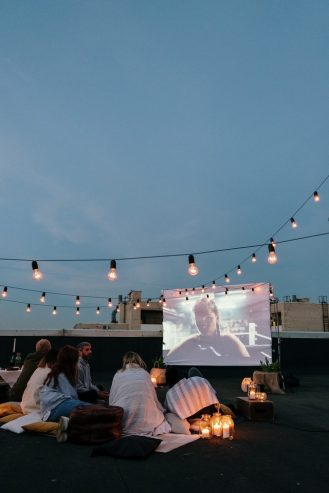 friends watching a movie on an LCD projector screen on top of a building