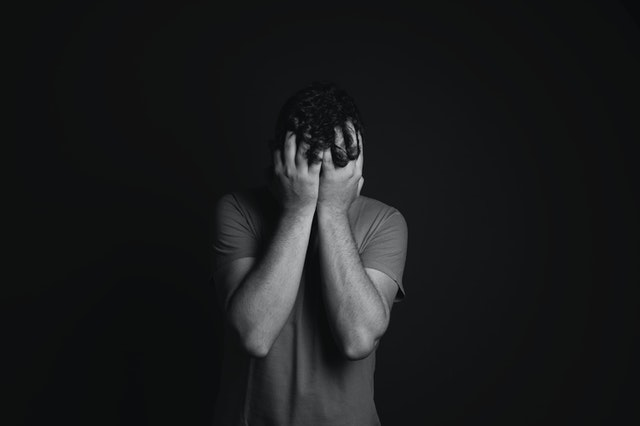 gray scale photo of man covering face with his hands