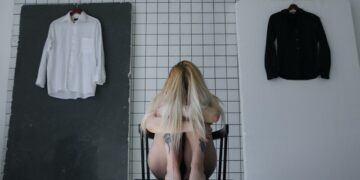 anonymous frustrated woman sitting on chair behind tiled wall