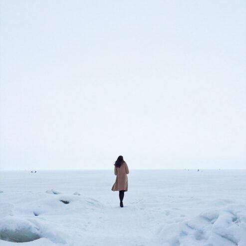 woman in brown coat on snow