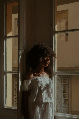 black woman standing near the window