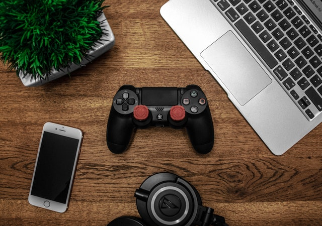 silver MacBook, black Sony ps4 dualshock4, silver iPhone 6 and round black keychain on brown wooden table