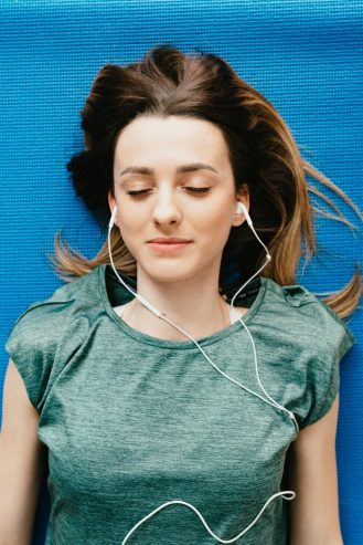 young woman listening to music in earphones in apartment