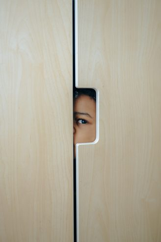 anonymous black little kid hiding in wardrobe