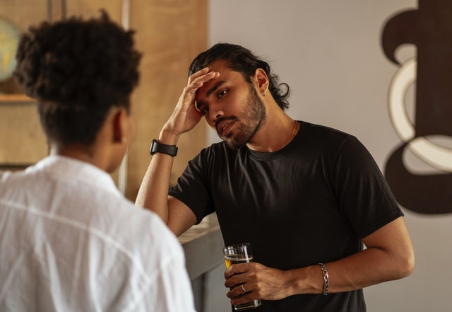 man talking to a woman with his right hand on his forehead with a glass of beer on his left hand