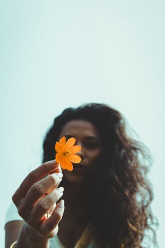 woman holding flower in her hand